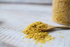 Nutritional yeast in a jar and also on the table in a spoon.